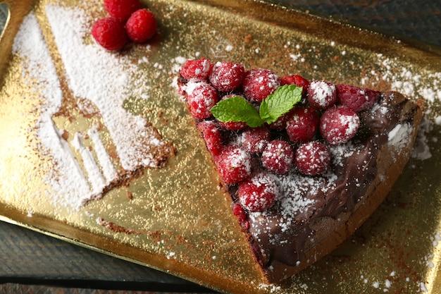 Bolo com cobertura de chocolate e framboesas na bandeja de madeira