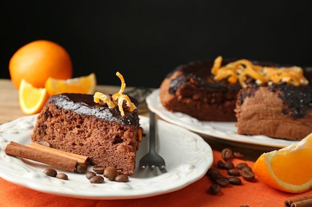 Bolo com cobertura de chocolate e laranja no prato, mesa de madeira, no escuro
