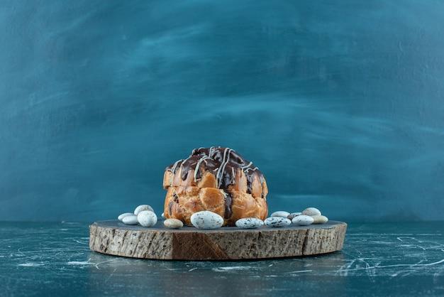 Bolo com cobertura de chocolate e pedras doces em uma placa em azul.