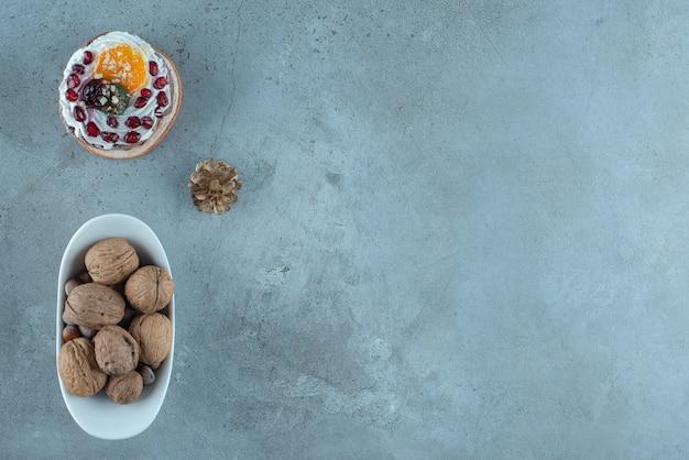 Bolo com cobertura de creme e frutas e uma tigela de nozes sortidas na superfície de mármore