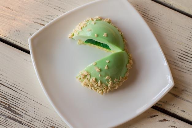Bolo com cobertura verde. sobremesa colorida no prato. bolo de musse cortado ao meio. delicioso presente para um amigo.