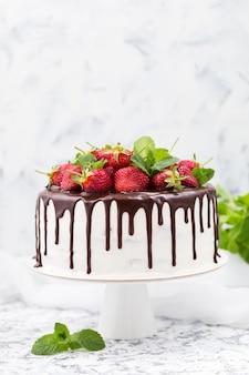 Bolo com creme branco, cobertura de chocolate e morangos.