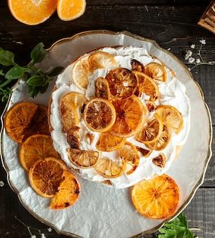Bolo com creme de limão e laranja secas na mesa