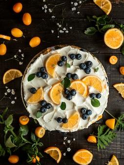 Bolo com creme de mirtilo limão kumquat e flores na mesa