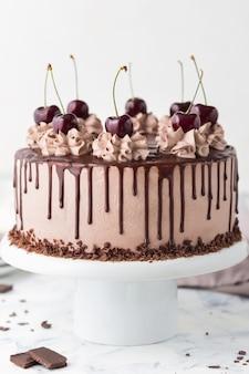 Bolo com creme de queijo café, cerejas e cobertura de chocolate em um carrinho de bolo branco