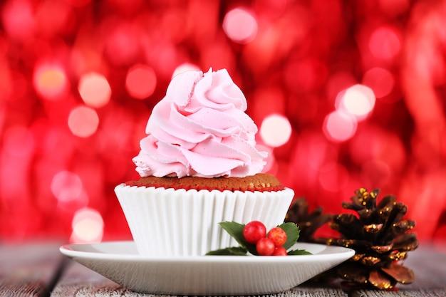 Bolo com creme no pires e decoração de natal na mesa de madeira e fundo brilhante