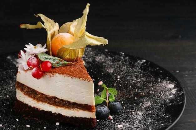 Bolo com frutas close-up. pedaço de bolo de musse com mirtilo, physalis e outras frutas vermelhas na placa preta