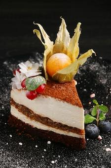 Bolo com frutas close-up. pedaço de bolo de musse com mirtilo, physalis e outras frutas vermelhas