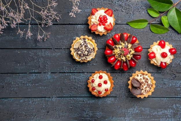 Bolo com frutas cornel, framboesa e chocolate rodeado de folhas de tortas em uma mesa de madeira escura com espaço de cópia