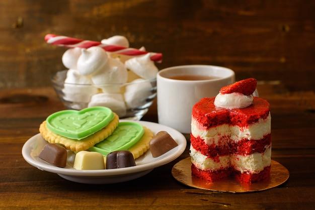 Bolo com morangos, biscoitos e uma xícara de café na mesa de madeira
