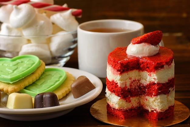 Bolo com morangos, biscoitos e uma xícara de chá em uma mesa de madeira