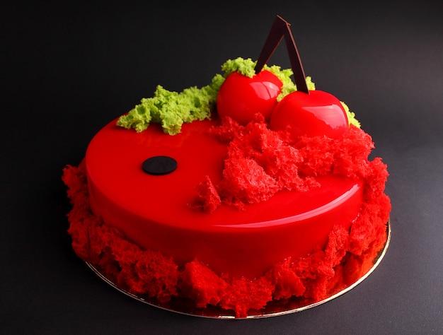 Bolo com mousse de baga no esmalte vermelho espelho decorado com um biscoito molecular. sobre o fundo preto.