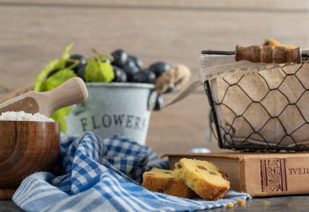 Bolo com passas, farinha e uvas na mesa de mármore com livro