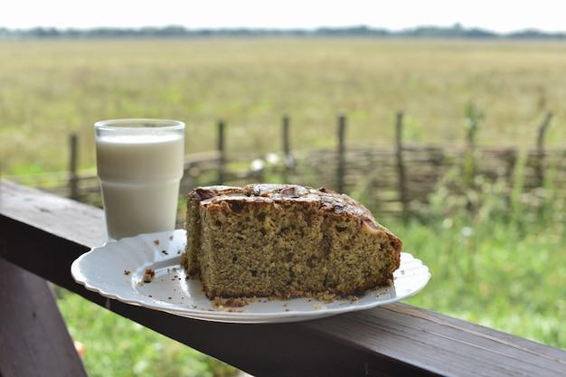 Bolo com sementes de papoula com um copo de leite. leite em um copo e bolo de semente de papoula em um campo