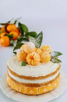Bolo com tangerina fresca e folhas em um fundo branco.
