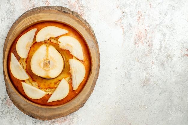 Bolo com vista de cima bolo apetitoso de pêra na placa de madeira do lado esquerdo da mesa de luz