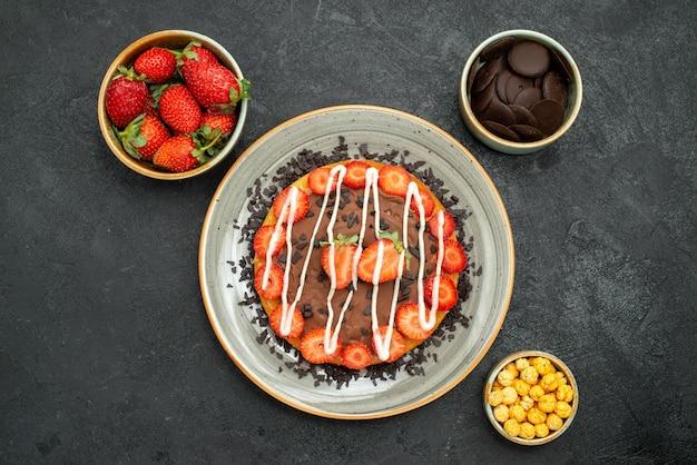 Bolo com vista de cima em close-up com bolo de chocolate apetitoso com chocolate e morango e tigelas de avelã de morango e chocolate no centro da mesa preta