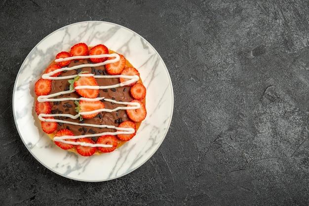 Bolo com vista de cima em close-up com morangos bolo apetitoso com morangos e chocolate no prato branco do lado esquerdo da mesa escura