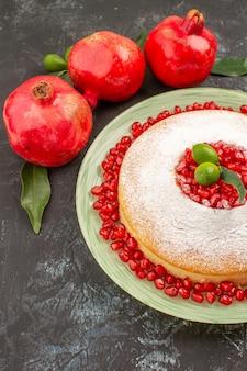 Bolo com vista de cima em close-up com romãs romãs com folhas e um bolo apetitoso