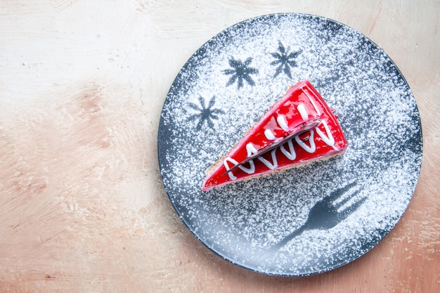 Bolo com vista de cima em close-up um bolo apetitoso com creme vermelho-branco e açúcar em pó no prato