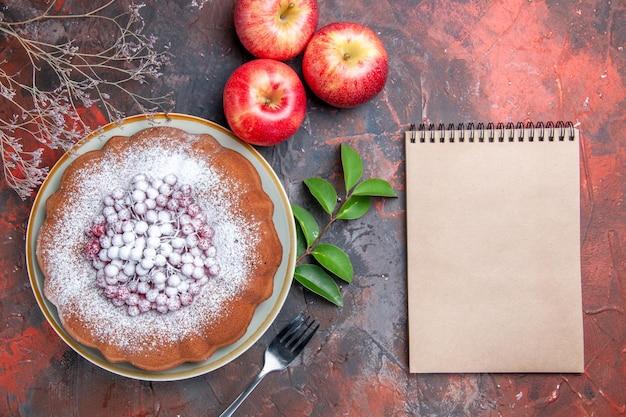 Bolo com vista de cima em close-up um bolo apetitoso com frutas garfo, maçãs, folhas, caderno branco