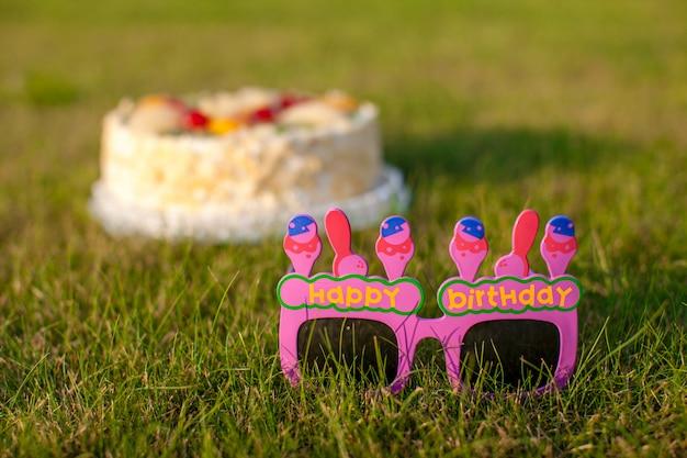 Bolo comemorativo e óculos que diz um feliz aniversário