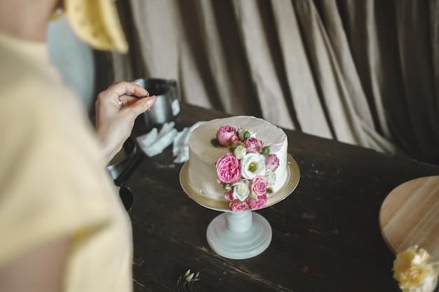 Bolo cremoso branco decorado com rosas em interior escuro