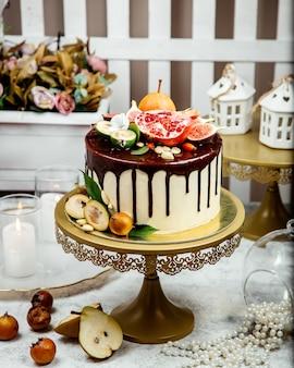 Bolo cremoso coberto com chocolate e várias frutas