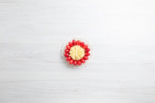 Bolo cremoso com dogwoods vermelhos em cima de uma mesa branca.