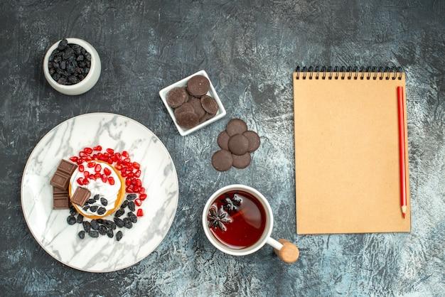 Bolo cremoso gostoso de vista de cima com biscoitos de chocolate e xícara de chá no fundo claro-escuro