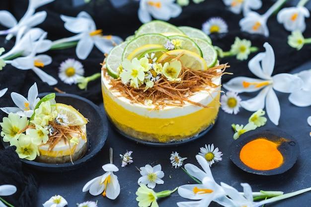 Bolo cru vegan com limão e lima em uma superfície preta coberta com pequenas flores de margarida