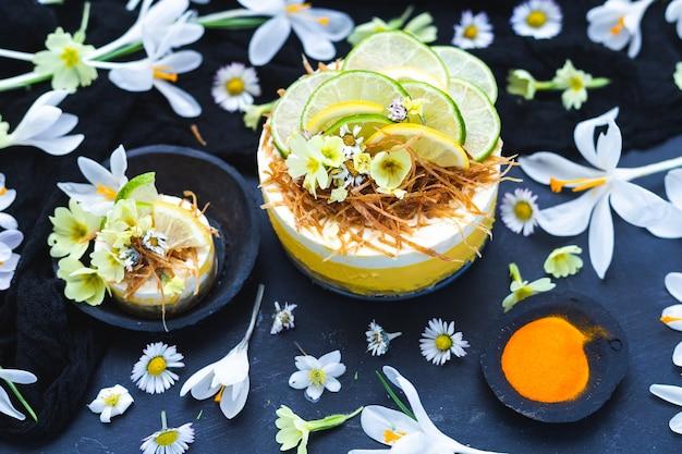 Bolo cru vegan com limão e lima em uma superfície preta coberta com pequenas flores de margaridas