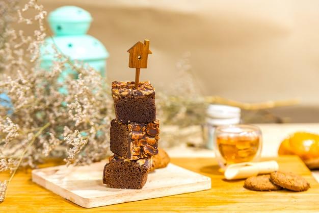 Bolo da brownie do chocolate com a porca de caju no fundo de madeira.