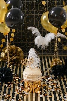 Bolo da festa de anos com os vários balões dourados e pretos da decoração.
