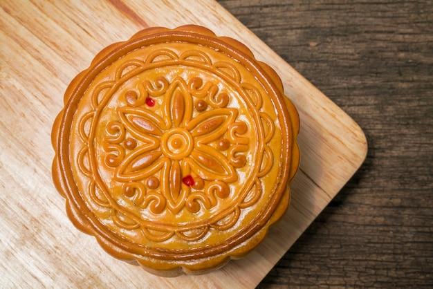 Bolo da lua para o festival chinês do meio-outono no tampo da mesa de madeira e fundo de madeira.