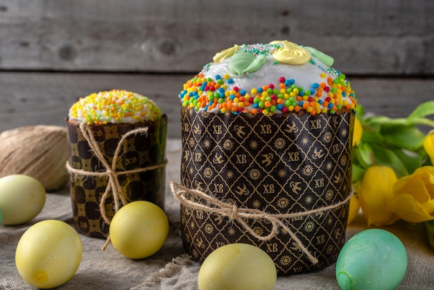 Bolo da páscoa, ovos pintados com tulipas em um fundo rústico velho de madeira.