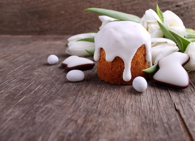 Bolo da páscoa, tulipas brancas, coelho do chocolate e ovos em um fundo de madeira. copie o espaço.
