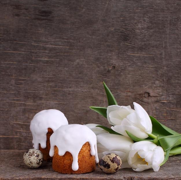 Bolo da páscoa, tulipas brancas, ovos de codorna em um fundo rústico de madeira.
