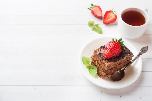 Bolo da trufa com chocolate e morangos e hortelã em uma tabela de madeira branca.