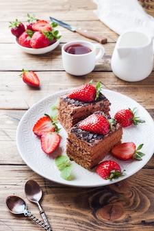 Bolo da trufa de chocolate com morangos e hortelã. mesa de madeira.