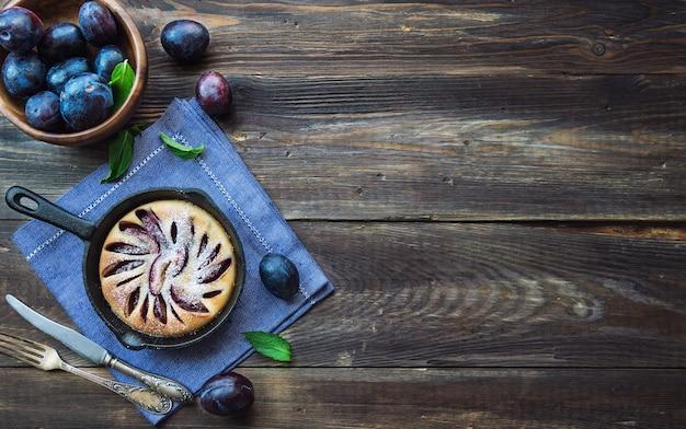 Bolo de ameixa caseiro fresco na frigideira de ferro na mesa de madeira rústica. vista do topo.