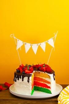 Bolo de aniversário arco-íris com frutas frescas sobre fundo amarelo