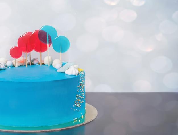 Bolo de aniversário azul do buttercream com pirulitos coloridos.