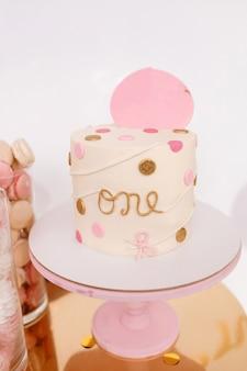 Bolo de aniversário bonito com decoração rosa para o aniversário de uma criança de um ano. barra de chocolate com biscoitos e marshmallows