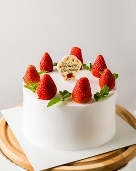 Bolo de aniversário branco com decoração de morango no bolo, fundo do conceito de comida.
