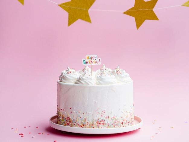 Bolo de aniversário branco e estrelas douradas