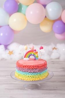 Bolo de aniversário colorido. bolo arco-íris com balões coloridos pastel. festa de aniversário.