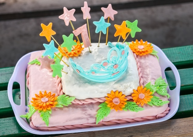 Bolo de aniversário com flores coloridas, estrelas e diadema