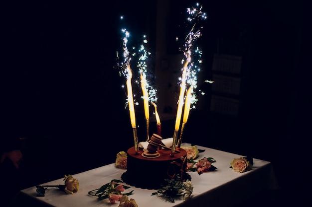 Bolo de aniversário com fogos de artifício na mesa