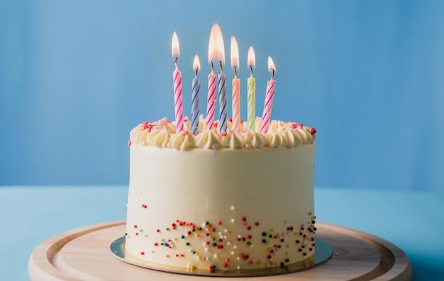 Bolo de aniversário com velas coloridas sobre fundo de cor azul